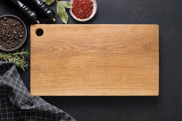 Deska do krojenia w kuchni z przyprawami i składnikami do gotowania na czarno. widok z góry.
