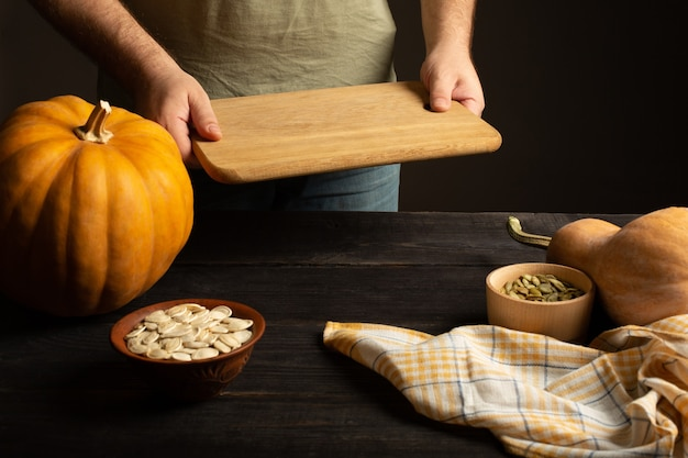 Deska do krojenia w męskich rękach. preparat do krojenia dyni. na czarnym drewnianym stole. nasiona w dwóch miseczkach.