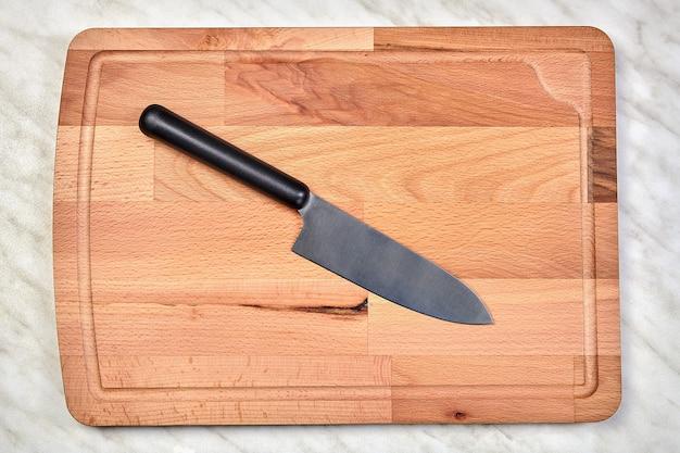 Deska do krojenia wykonana z drewna brzozowego z nożem kuchennym na jej powierzchni.