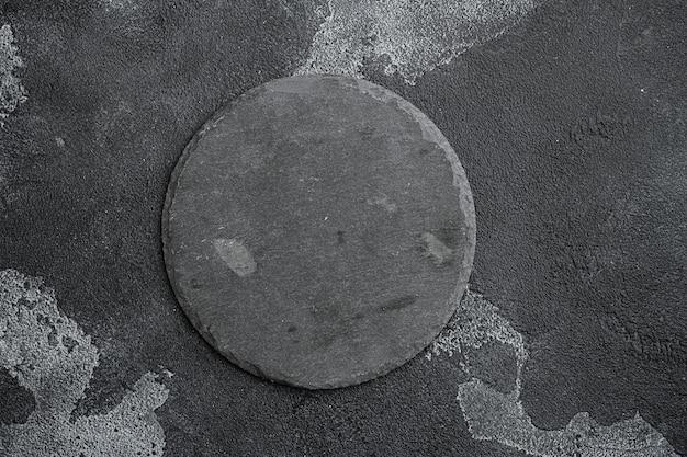 Deska do krojenia z czarnego kamienia z kopią miejsca na tekst lub jedzenie z kopią miejsca na tekst lub jedzenie, widok z góry płasko leżący, na tle czarnego ciemnego kamiennego stołu