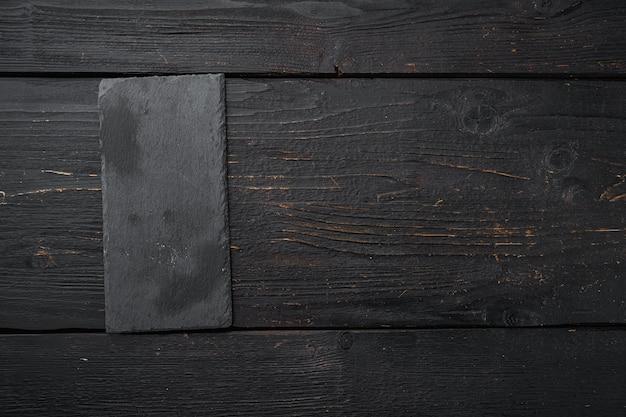 Deska do krojenia z czarnego kamienia z miejsca kopiowania tekstu lub żywności z miejscem kopiowania tekstu lub żywności, widok z góry płasko leżał, na tle czarnego stołu drewnianego