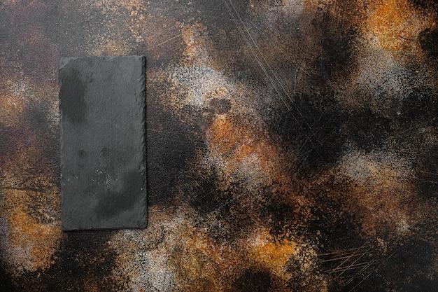 Deska do krojenia z kamienia łupkowego z kopią miejsca na tekst lub jedzenie z kopią miejsca na tekst lub jedzenie, widok z góry płasko leżał, na starym ciemnym, rustykalnym tle stołu
