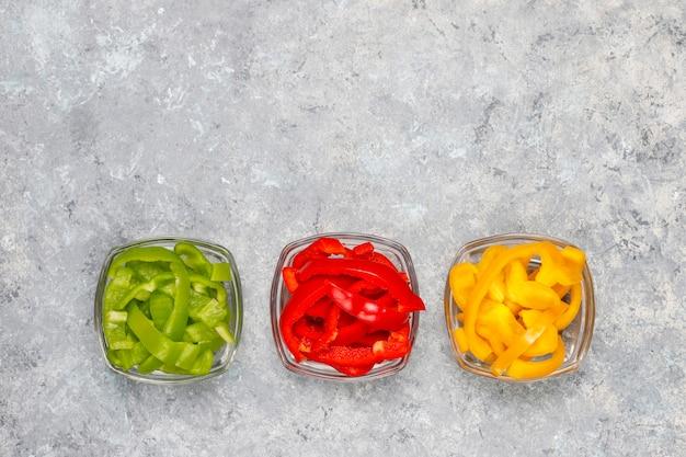 Deska do krojenia z kawałkami kolorowej papryki na lekkiej powierzchni. pokrojeni słodcy pieprze w różnych kolorach, jarzynowy sałatkowy składnik, gotuje zdrowego jedzenie, odgórny widok