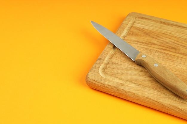 Deska do krojenia z nożem na pomarańczowym tle.