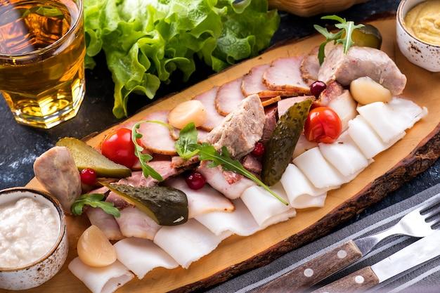 Deska do krojenia z różnymi krojonymi wędzonymi produktami mięsnymi i smalcem. zbliżenie