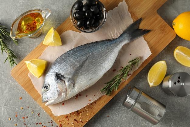 Deska do krojenia z rybą dorado i przyprawami na szaro