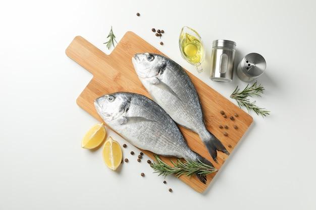 Deska do krojenia z rybami dorado i gotowania składników na białym tle