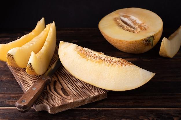 Deska do krojenia z soczystymi plastrami melona i pół na ciemnym tle drewnianych, zdrowa żywność.