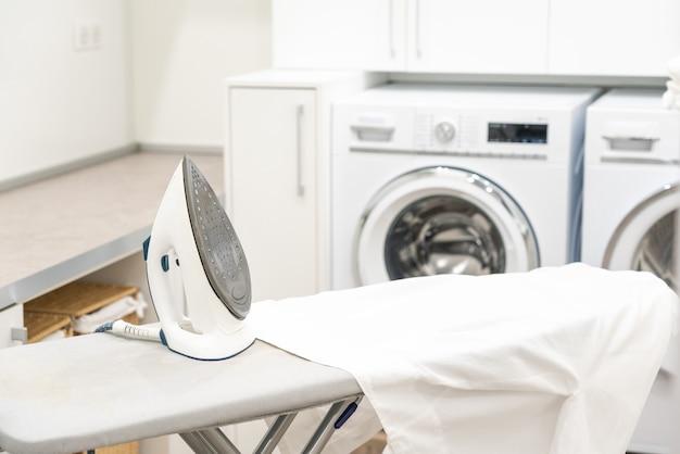 Deska do prasowania z białą koszulą i żelazkiem w pralni
