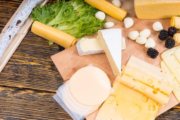 Deska do serów dla smakoszy z dużym kątem, zawierająca różnorodne sery, wędliny i świeże owoce podawane na rustykalnym drewnianym stole z słojami drewna i miejscem na kopię