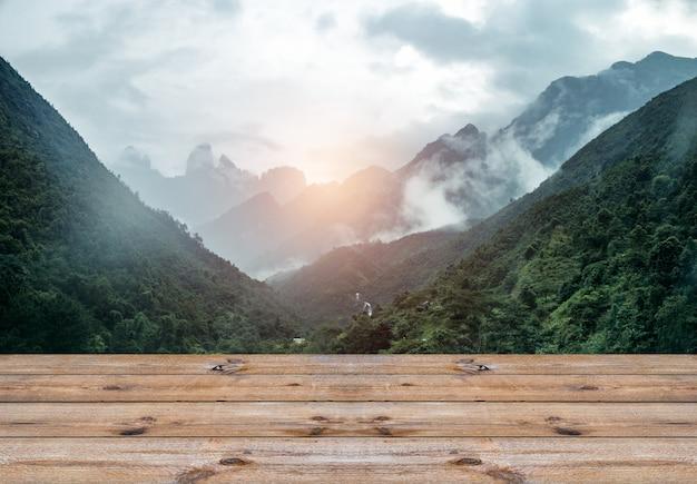 Deska drewniana na paśmie górskim ze sceną z efektem mgły i światła słonecznego