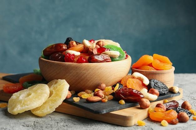 Deska i miski z suszonymi owocami i orzechami na szarym stole