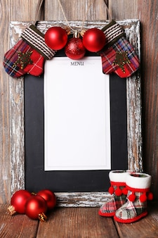 Deska menu z dekoracją świąteczną na tle drewnianych desek