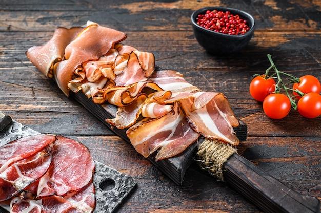 Deska mięsna antipasto, pancetta, salami, szynka krojona, kiełbasa, prosciutto, boczek. ciemne tło drewniane. widok z góry.