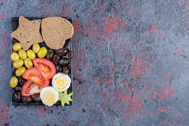 Deska przekąskowa z jajkami, pomidorem i oliwkami.