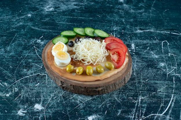 Deska przekąskowa z sałatką i warzywami.