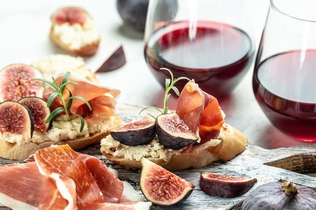Deska przystawek z zestawem tradycyjnych hiszpańskich tapas. włoskie antipasti bruschetta z prosciutto, twarogiem i figami do wina. widok z góry.