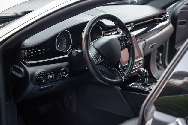 Deska rozdzielcza samochodu i kierownica z przyciskami sterowania multimediami. czarny kokpit. luksusowe wnętrze pojazdu. tło na temat samochodów.