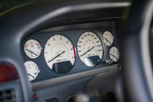 Deska rozdzielcza samochodu oraz szczegóły prędkościomierza i obrotomierza