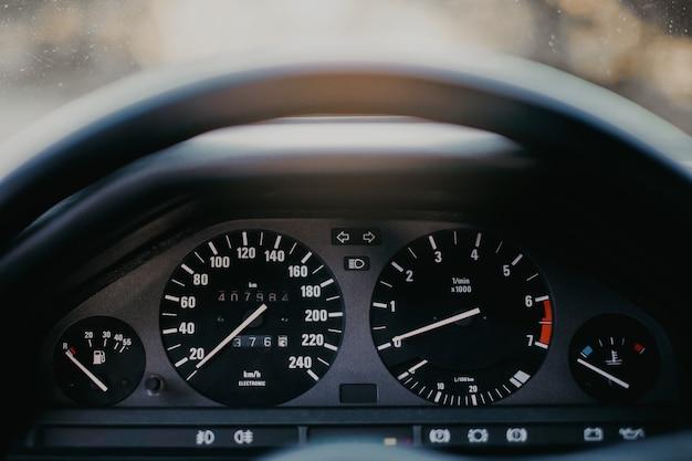 Deska rozdzielcza samochodu w stylu retro z analogowym prędkościomierzem, obrotomierzem i licznikiem kilometrów.