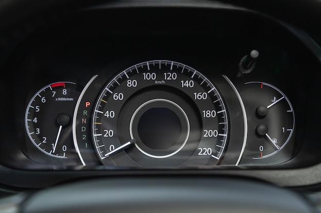 Deska rozdzielcza samochodu z białym podświetleniem: licznik kilometrów, prędkościomierz, obrotomierz, poziom paliwa, temperatura wody i inne