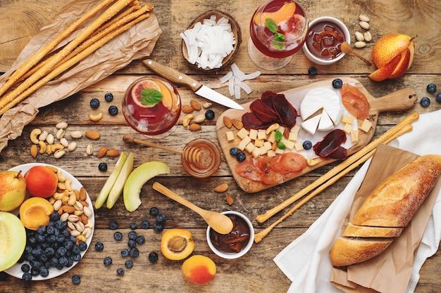 Deska serów, różnego rodzaju przekąski, owoce, orzechy, bagietka na drewnianym stole. styl rustykalny. francuska impreza degustacyjna, biesiadna sceneria.