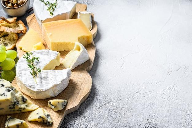 Deska serów z francuskim camembertem, brie, parmezanem i serem pleśniowym, winogronami i orzechami włoskimi. białe tło. widok z góry. skopiuj miejsce.