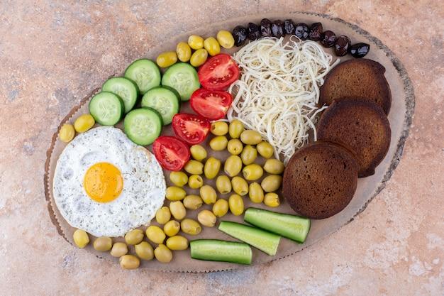 Deska śniadaniowa z jajkiem sadzonym i sałatką jarzynową
