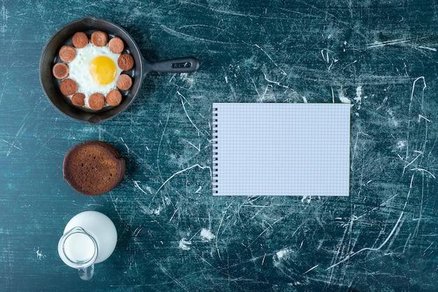 Deska śniadaniowa z jajkiem sadzonym, kiełbasą i naleśnikami.