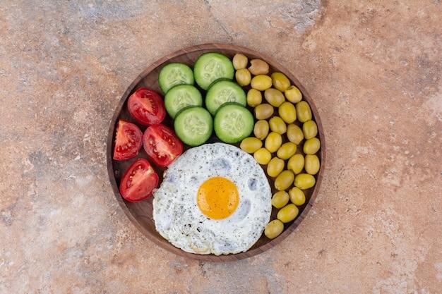 Deska śniadaniowa z kromkami chleba, warzywami i jajkiem