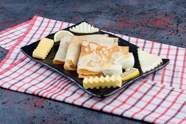 Deska śniadaniowa z naleśnikami, serem, cytryną i jajkami.
