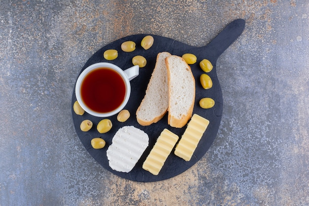 Deska śniadaniowa z pieczywem i filiżanką herbaty