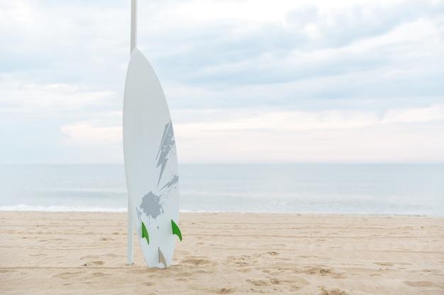 Deska surfingowa na piasku na słonecznej plaży