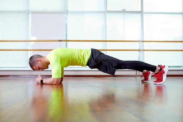 Deska to pewnie umięśniony młody człowiek ubrany w odzież sportową i robiący pozycję deski podczas ćwiczeń na podłodze we wnętrzu loftu