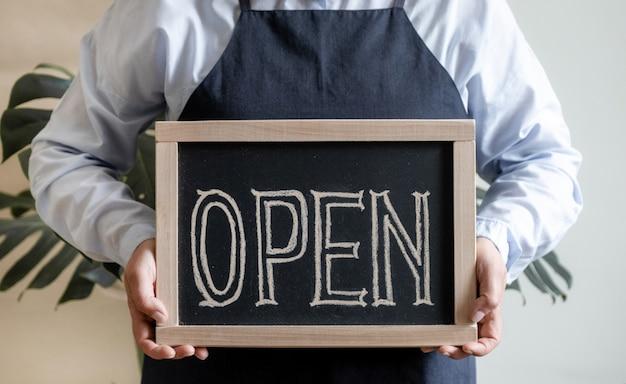 Deska trzymać ręce z otwartym tekstem. pracownik w fartuchu pokazuje otwarcie kawiarni lub rynku.