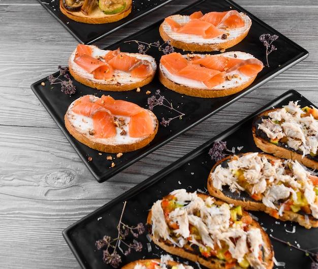 Deska wędlin i serów z wędlinami i różnymi rodzajami serów. wędzone mięso z czarnego talerza. deska z pysznym parmezanem, dorblu, miękkim serem, camembertem.