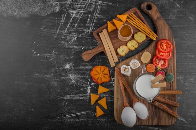 Deska z frytkami, krakersami i ciastkami na drewnianym talerzu pośrodku