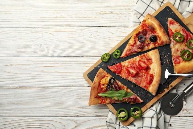 Deska z kawałkami smacznej pizzy na białym drewnianym stole