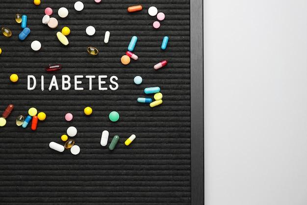 Deska z pigułkami i słowem cukrzyca na białym tle