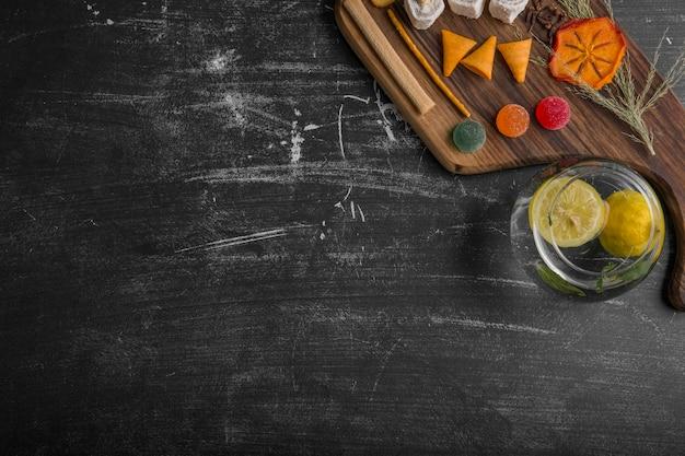 Deska z przekąskami i ciastami z ziemniakami w wodzie na czarnym tle, widok z góry