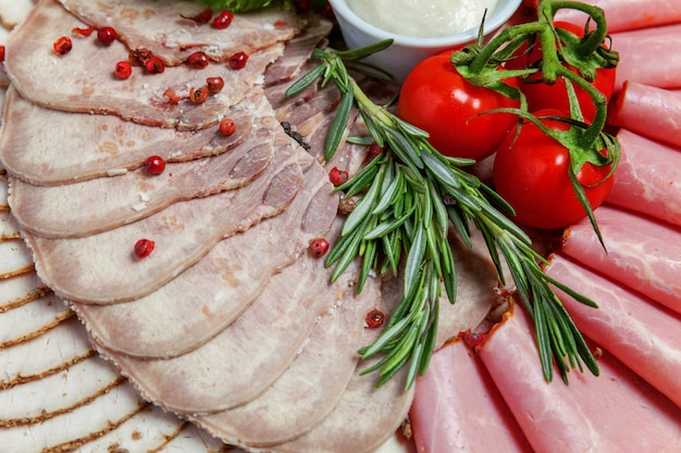 Deska z różnymi rodzajami przysmaków mięsnych i szynkowych, sosem i świeżymi warzywami. talerz w menu restauracji