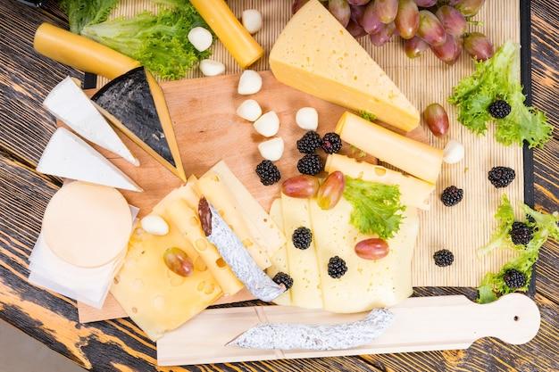 Deska z serami dla smakoszy z wysokiego kąta z rozmaitymi serami, wędlinami i przyozdobionymi świeżymi owocami, podana na rustykalnym drewnianym stole
