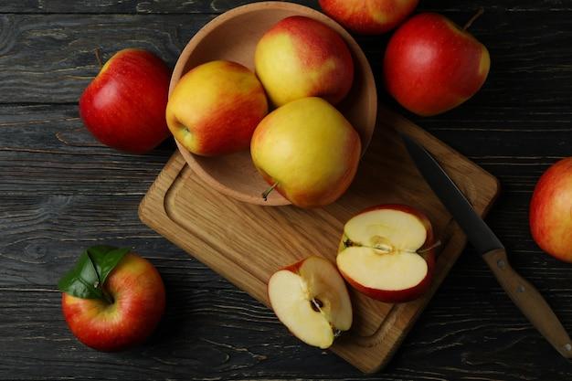 Deska z smacznymi czerwonymi jabłkami na drewnianym stole
