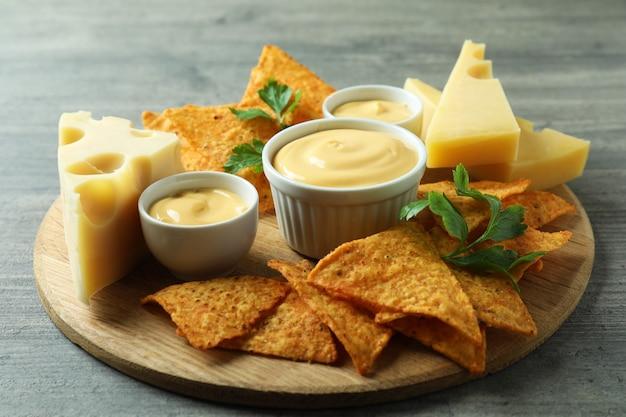 Deska z sosem serowym, frytkami, serem i pietruszką na szarym teksturowanym stole