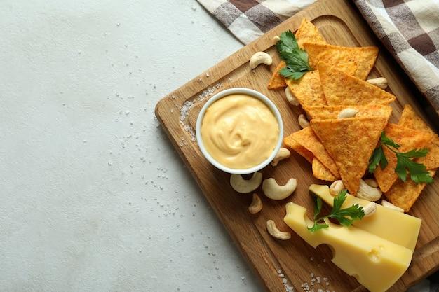 Deska z sosem serowym i przekąskami na białym teksturowanym stole