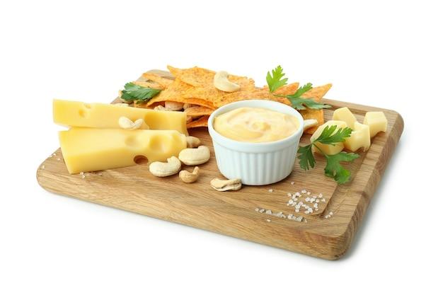 Deska z sosem serowym i przekąskami na białym tle