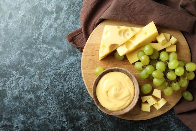 Deska z sosem serowym, winogronami i serem na czarnym stole smokey z ręcznikiem kuchennym