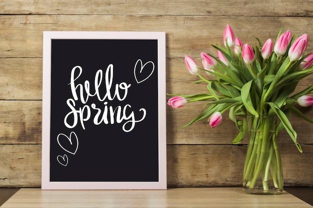 Deska z tekstem hello spring, wazon z tulipanami na drewnianej powierzchni. pojęcie nadejścia wiosny, święta.