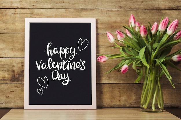 Deska z tekstem szczęśliwych walentynek, wazon z tulipanami na drewnianej powierzchni.