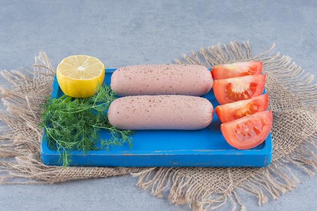 Deska ze smacznymi kiełbaskami, pomidorem i cytryną na desce.